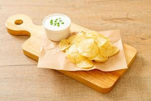 Potato chips with sour cream dipping sauce photo