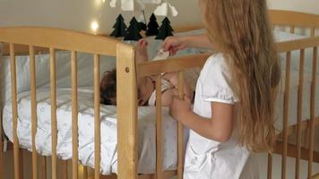 Girl preschool girl stands at the crib with a child soothes her Caring for a little sister video