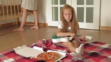 Preschooler girl eating pizza while sitting on floor in room video
