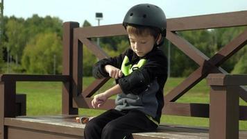 un garçon est assis sur un banc dans le parc video