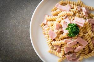 Spirali or spiral pasta mushroom cream sauce with ham - Italian food style photo