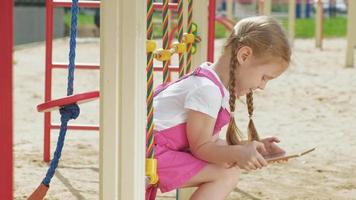 Preschool girl playing with a tablet outdoors video