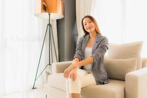Portrait beautiful young asian women happy smile relax sitting on sofa chair photo