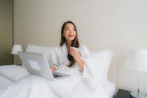 Retrato de hermosas mujeres asiáticas jóvenes con taza de café y computadora portátil en la cama foto