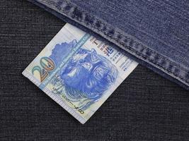 Hong Kong banknote of twenty dollars between blue denim fabric photo