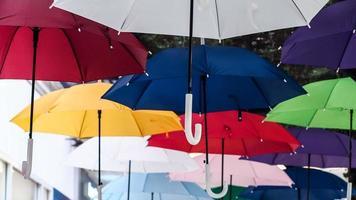 calle decorada con sombrillas de colores. muchos paraguas coloreando el cielo de la ciudad foto