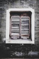 Old Wooden Louver Window on Brick Wall. Vertical Style old rustic brick background photo