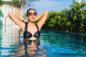 Portrait beautiful young asian women happy smile relax outdoor swimming pool in resort photo