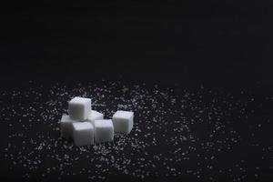 Terrones de azúcar blanco sobre fondo negro foto