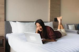 Portrait beautiful young asian women using computer and mobile phone on bed photo