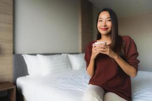 retrato, hermoso, joven, mujeres asiáticas, con, taza de café, en cama foto