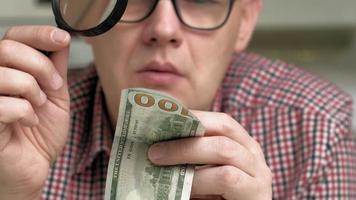 el hombre comprueba dólares falsos video