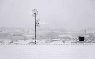 Snowy roofs and antennas photo