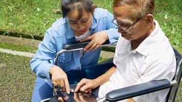 avô em cadeira de rodas no tablet video