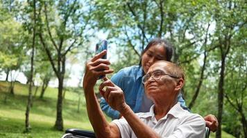 abuelo en silla de ruedas en el teléfono celular video