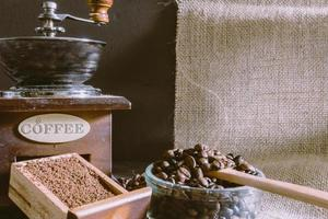 Still life with coffee beans and old coffee mill on the rustic background photo
