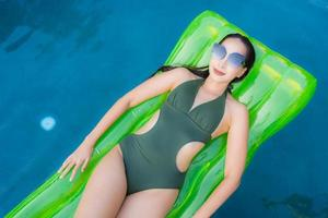 Portrait beautiful young asian woman smile happy relax and leisure in the swimming pool photo