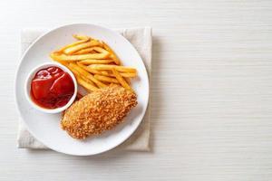 Filete de pechuga de pollo frito con papas fritas y salsa de tomate foto