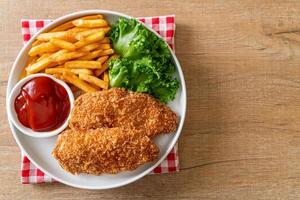Fried chicken breast fillet steak with French fries and ketchup photo