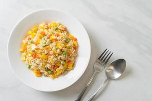 Homemade fried rice with mixed vegetable of carrot, green bean peas, corn, and egg photo