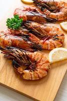 Grilled tiger prawns or shrimps with lemon on a plate photo