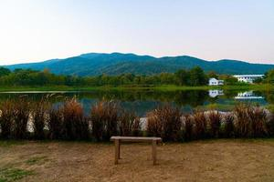 Wood bench with a beautiful lake at Chiang Mai with forested mountain and twilight sky in Thailand photo