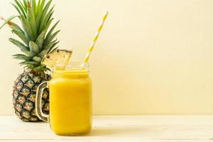 Fresh pineapple smoothie glass on wood table - Healthy Drink photo