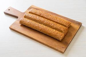 Fried Chinese fish cake or fish ball line on wood board photo