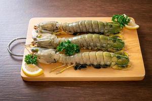 Fresh mantis shrimp with lemon on a board photo