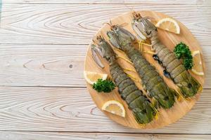 Camarones mantis frescos con limón sobre una tabla foto