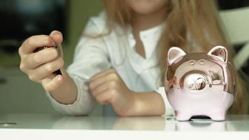 Girl puts money in a pink piggy bank video