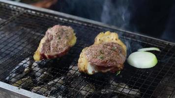 Steaks auf dem Grill über der Holzkohle braten und Gemüse drumherum hinzufügen video