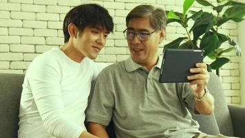 Father and son using digital tablet at home video