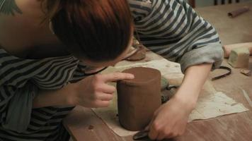 A ceramist sculpts a clay mug and smooths the edges of the clay base with a tool video