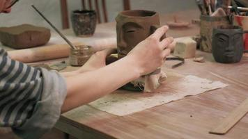 Close-up of a ceramist sculpting a mug with the image of a face video