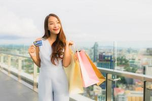 Portrait beautiful young asian woman happy and smile with credit card for shopping bag from department store photo