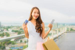 retrato, hermoso, joven, mujer asiática, feliz, y, sonrisa, con, tarjeta de crédito, y, móvil, o, teléfono inteligente, y, bolsa de compras foto