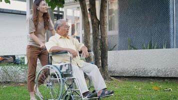 Disabled senior man on wheelchair with daughter, Happy Asian generation family having fun together outdoors backyard, Care helper young woman walking an elderly man smiling and laughed, slow motion video