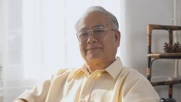 retrato asiático, rosto feliz, idoso sênior, sentado em uma cadeira de rodas, sorrindo em uma casa de repouso, closeup deficiente paciente olhando para a câmera, cuidados de saúde para idosos, câmera lenta video