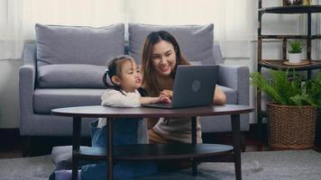 Asian young mother with laptop computer teaching her kid to learn or study online in living room at home, Mum and little preschool daughter learning online on computer, family homeschooling online video