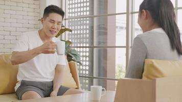 Happy Asian beautiful lifestyle family couple husband and wife laughing sitting in a cafe drinking coffee having talking conversation together inmorning. Two people in cafe enjoying video