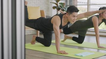 Happy Asian beautiful lifestyle family couple doing YOGA standing meditating on virabhadrasana 3 pose workout at home together on mat. Two people sport healthy concept video
