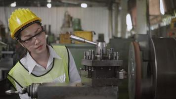 ingénieur mécanicien professionnel asiatique ou femme d'opération portant des lunettes de sécurité uniformes travaillant sur un atelier de tour à métaux usine de fabrication industrielle, femme d'ouvrier de tour d'industrie lourde, mouvement lent video