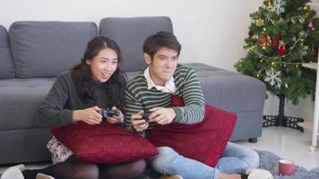 Happy Asian beautiful young family couple husband and wife smile and laugh enjoying funny with each other playing video game, holding joysticks console. Happiness and gaming concept.