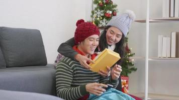 Happy Asian beautiful young family couple husband and wife in home living room, woman hide surprise giving gift box her boyfriend present during play smartphone, winter holidays and valentine concept video