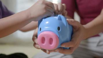 Happy Asian kid boy preschool and mother putting pin money coins into piglet. Little child putting coin into piggy bank for saving with pile of coins at home, Investment education concept video