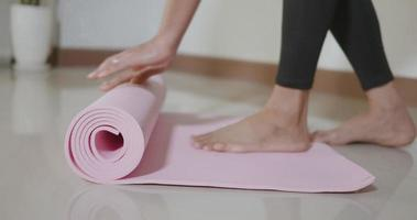 Woman yoga at home, female rolling up exercise pink yoga mat before exercising on floor in living room, Healthy sport fit lifestyle video