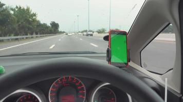 la carte de navigation gps sur un smartphone moderne à écran vert gadget monté sur un support de téléphone dans le tableau de bord de la voiture en conduisant sur l'autoroute aller à destination video