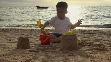 Little boy playing sand with toy sand tools at a beach video