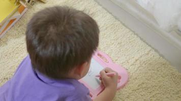 Happy Asian klid little boy preschool writing at the magnetic drawing board at home on carpet video